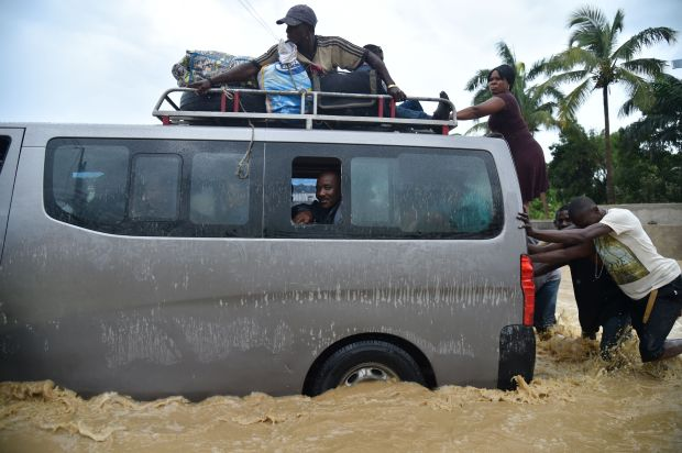 TOPSHOT - People try to cross the overflowing La Rouyonne river in the commune of Leogane, south of Port-au-Prince, October 5, 2016. Haiti and the eastern tip of Cuba -- blasted by Matthew on October 4, 2016 -- began the messy and probably grim task of assessing the storm's toll. Matthew hit them as a Category Four hurricane but has since been downgraded to three, on a scale of five, by the US National Hurricane Center. Hector Retamal, AFP/Getty Images