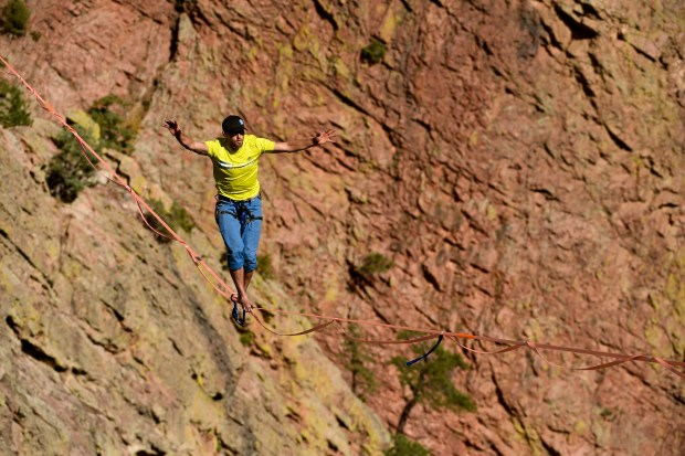 Taylor VanAllen, 24, makes the FA, or First Across, on a high-line from the Wind Tower rock formation to the Bastille rock formation 450 feet off the ground and just shy of 600 feet across in Eldorado Canyon State Park on October 15, 2016 in Golden, Colorado. VanAllen, an athlete with Slackline Industries, recreated the historic Ivy Baldwin high line crossing of Eldorado Canyon in a benefit for trail building at the state park.  VanAllen crossed from the exact location as the legendary Baldwin.  Baldwin, who was a high wire performer, did the crossing on a high wire over 80 times in his lifetime. The last time he made the 600 foot walk was on his 82nd birthday in 1948. VanAllen's walk was the first ever by a High Line walker on a slack line.