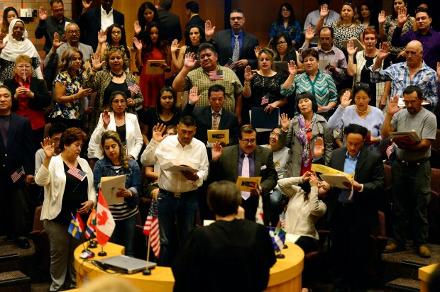 Individuals raise their right hands as they pledge the Oath of Allegiance during a naturalization ceremony to become United States citizens presented by the Littleton Immigrant Resources Center at the Littleton Center Council Chamber on September 29, 2016.