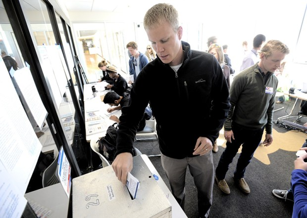 A voter drops his ballot into a ballot box at the University of Colorado in Boulder last Wednesday.