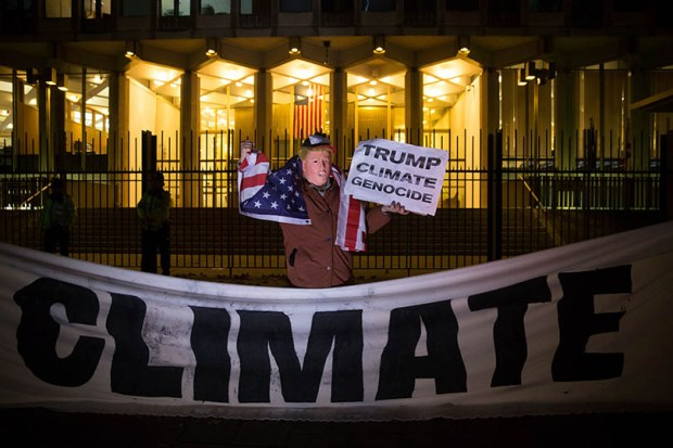 A protester poses with a sign during a demonstration against President-elect Donald Trump's vow to withdraw the U.S. from the Paris climate accord outside the U.S. Embassy in London on Nov. 18.