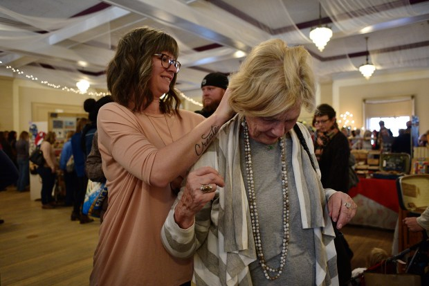 Erin Trumble (left), owner of Sparkle and Stone, helps Barbara Connolly with a necklace, during the 2016 Horseshoe Holiday Market inside the Highlands Masonic Temple in Denver, Nov. 26, 2016.