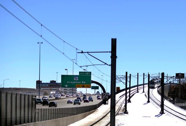 Traffic moves along on Interstate 25 in Denver as an RTD light rail train travels on the adjacent tracks.