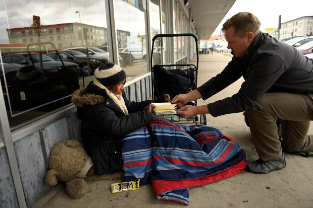 Kevin Raleigh, right, outreach team leader with the Colorado Coalition for the Homeless, talks to Skye Vehr on Nov. 22, 2016, along South Broadway as he makes sure she is prepared for the coming cold, offering socks, hats and blankets, and talking to her about shelters.
