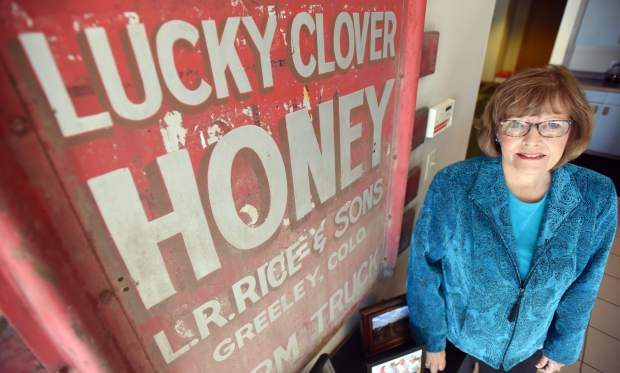 Ronna Rice stands alongside one of the original signs for Rice's Honey on display at Rice's Honey in Greeley.