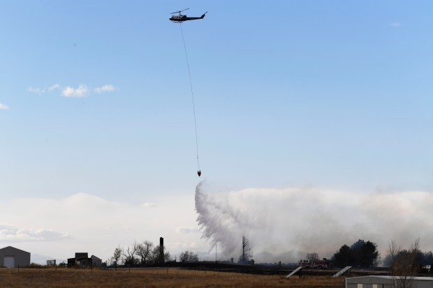 A helicopter makes a water drop near a home that burned down to the ground near Watkins November 16, 2016.