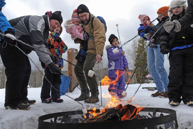 Visitors pause a sleigh ride at Snow Mountain Ranch, near Granby, to roast marshmallows on an open fire.