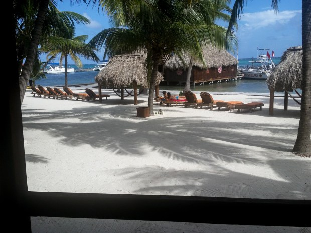 The view from a thatched-roof cabana at Ramon's Village in San Pedro, Belize, with dive boats tied up to the pier in the distance. Ramon's is one of the oldest dive companies in Belize; over 40 dive sites are within a 15 minute boat ride.