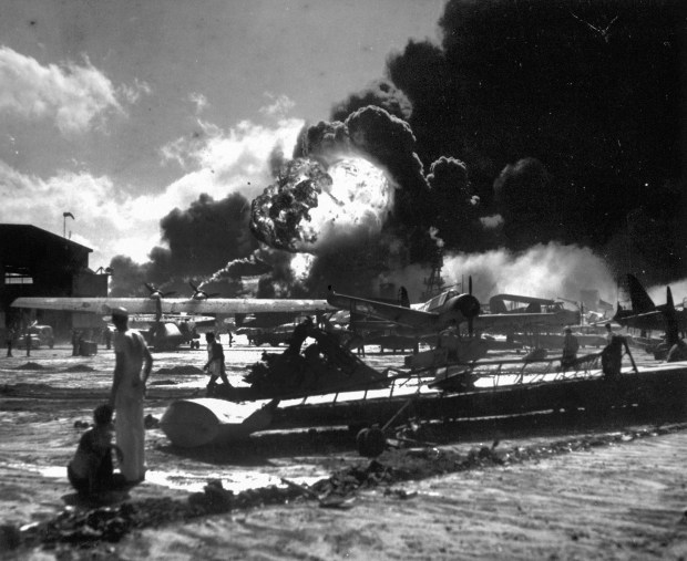 In this Dec. 7, 1941 photo provided by the U.S. Navy, sailors stand among wrecked airplanes at Ford Island Naval Air Station as they watch the explosion of the USS Shaw, background, during the Japanese surprise attack on Pearl Harbor, Hawaii.