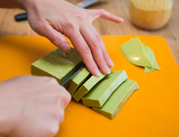 "Angela Huang slices a block of zucchini ""cheese,"" made with ingredients that follow the Autoimmune Protocol diet."