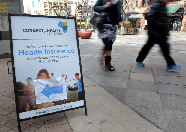 A sign placed out on the 16th Street Mall, beckons people to sign up for health insurance through the Affordable Care Act in 2014.