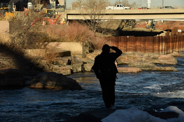 Adam Vo takes pictures of work that continues on the trickier-than-expected project at the new riverfront plaza at Confluence Park on Dec. 29, 2016, in Denver.