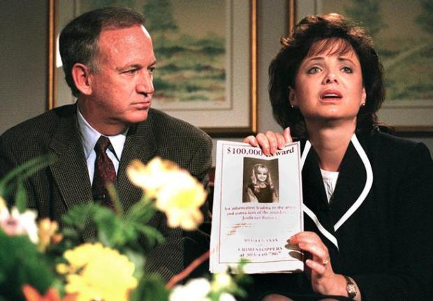 John Ramsey looks on as his wife Patsy Ramsey holds an ad promising a reward for information leading to the conviction of the killer of their 6-year-old daughter, JonBenet, during a television interview on May 1, 1997.