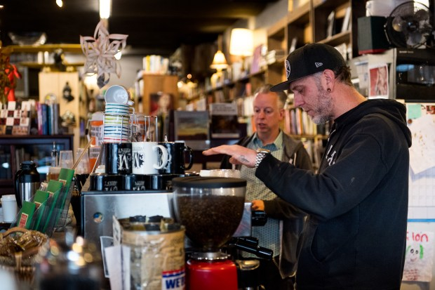 Owner Jim Norris, right, and co-owner Matt Megyesi work behind the coffee counter at Mutiny Information Cafe on December 2, 2016, in Denver. Norris and Megyesi intend to apply for a social marijuana use permit, perhaps to host a monthly event allowing marijuana, once the city's Department of Excise and Licenses works out the particulars of how to implement Initiative 300.