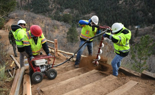 Timberline Landscaping workers dig a post hole as they install a railing along a lower portion of the Manitou Incline Monday, November 28, 2016. The Incline will reopen Friday, December 2 after being closed for more than three months. Photo by Mark Reis, The Gazette