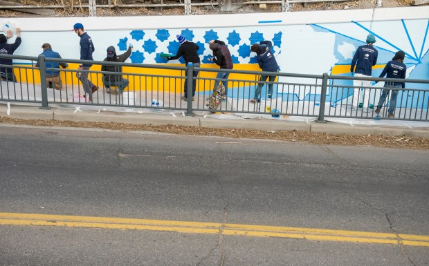 Volunteers and artists paint a large mural along part of the 38th Street underpass near Blake Street on Dec. 3 as part of a RiNo community art project.