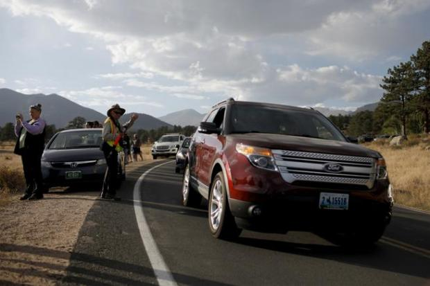 In this file photo, volunteer Karla Henderson directs traffic on a busy September day in 2015 during elk season at Rocky Mountain National Park.