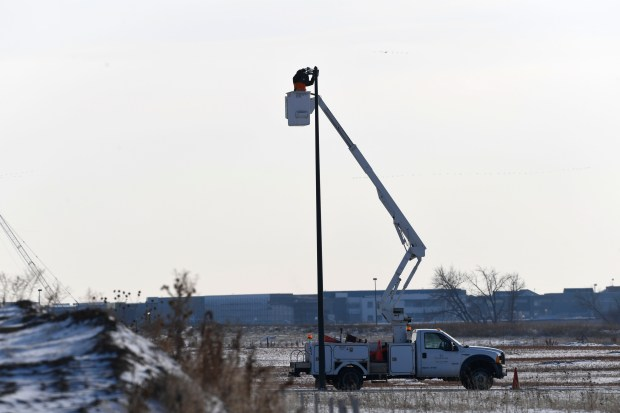 An electrician from Guarantee Electric works on upgrading an LED street lamp by adding a photo controller to it integrating the lights a smart system at the Panasonic facility near Denver International Airport Dec. 7, 2016.