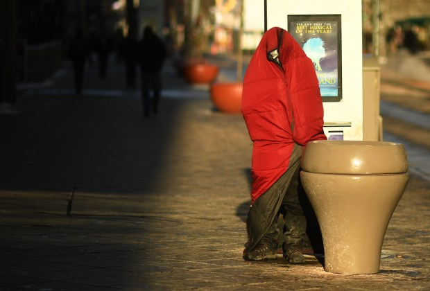 A homeless man tries to stay warm in frigid temperatures in Denver, December 08, 2016. Temperatures dropped below zero overnight.