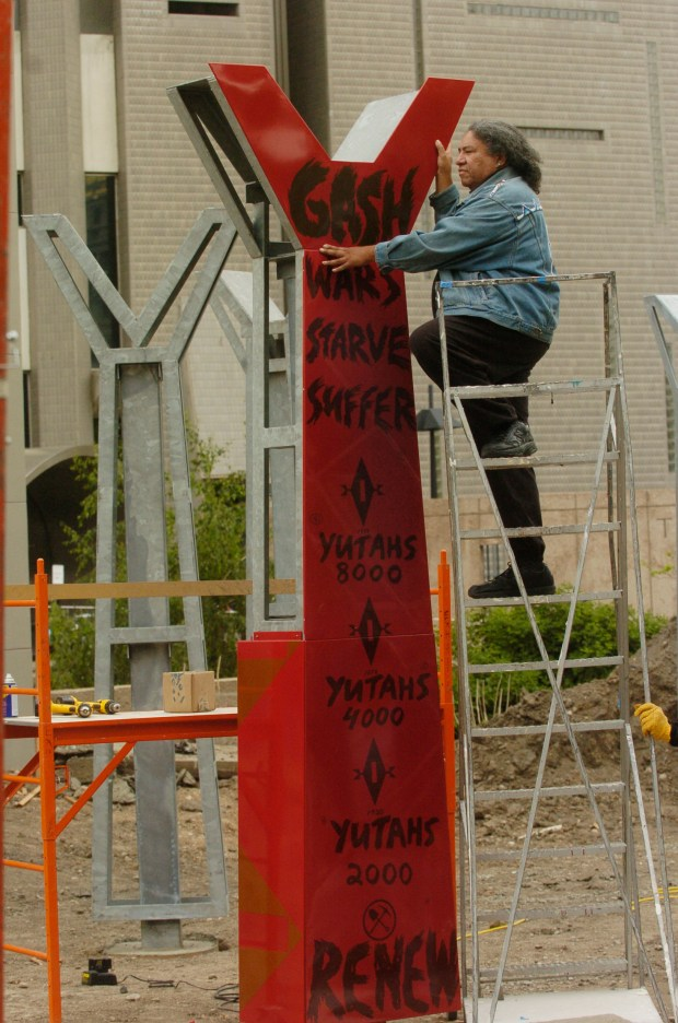 """Artist Edgar Heap of Birds stands on a ladder checking one of 10 of the red porcelain- enameled standing forms that stands 12 feet tall as a part of the """"Wheel"""" sculpture at the Denver Art Museum May 24, 2005."""