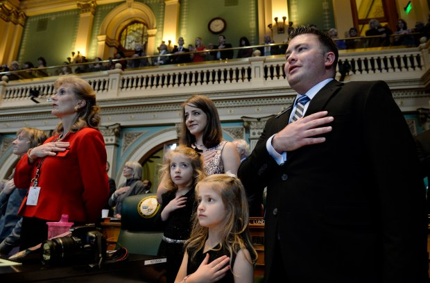 Rep. Patrick Neville and his wife Kristi and their daughters, Hannah, 3, and Mary Katelyn, stand for the national anthem during the opening of the Colorado legislature at the State Capitol in Denver Jan. 7, 2015.