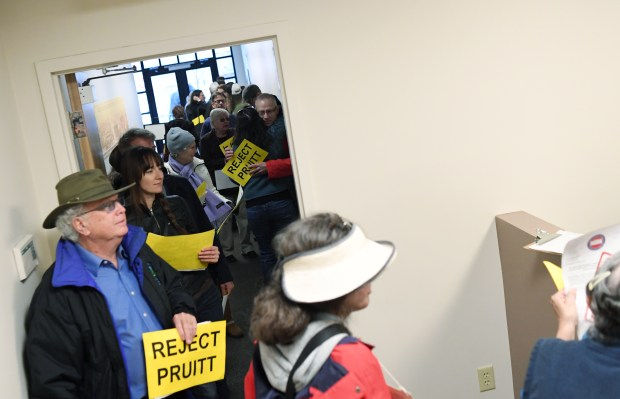 """Activists gather line up in the hallway of Sen. Michael Bennet's office, in Denver, to oppose, """"TrumpÕs nominee for EPA Administrator, Oklahoma Attorney General Scott Pruitt, January 23, 2017. About 40 activist handed rejection letters to workers in Bennet's office."""