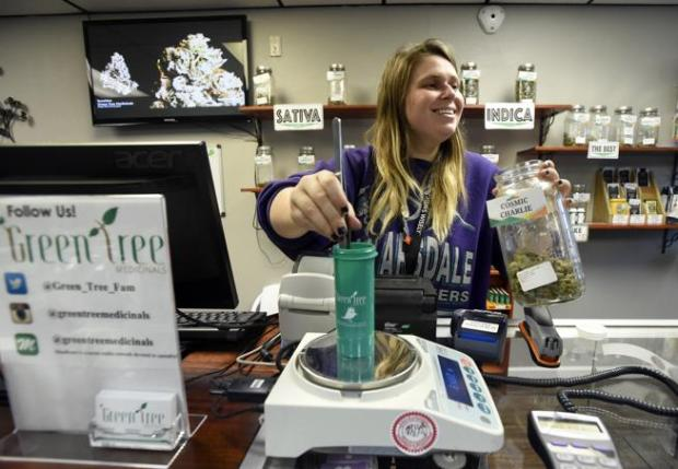 General Manager Laura Raab laughs while weighing marijuana for a customer at Green Tree Medicinals on Tuesday in Boulder.