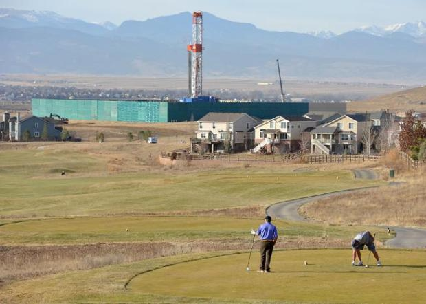 Golfers play a round at the Vista Ridge Golf Club with a drilling rig in the background in Erie in 2014. Lafayette leaders tabled an ordinance that would sanction non-violent protests and acts of civil disobedience against fracking operations.
