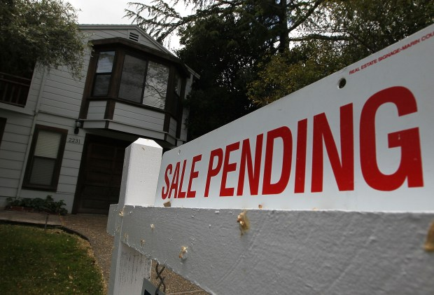 "A ""sale pending"" sign is displayed in front of a home for sale."