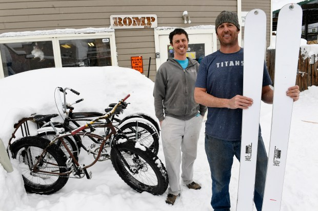 Brother Morgan, left, and Caleb Weinberg, holding a pair of the newly made skiw for the 10th Mountain Division, are pictured outside of the headquarters of their ski company Romp Skis on January 12, 2017 in Crested Butte, Colorado. Brothers Caleb and Morgan Weinberg, who started Romp Skis in Crested Butte in 2010, recently landed a contract to press several hundred skis for soldiers in the 10th Special Forces. The company, which makes all their skis by hand, specializes in progressive custom ski designs with custom flex and camber.