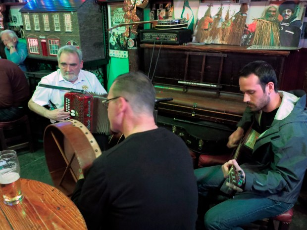 At a pub in Dingle, Ireland, a musician holds a bodhran, which is an Irish handheld drum.