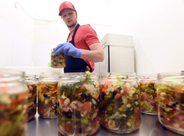 Miles Kiefer fills the jars with ingredients as he prepares soup for Mason Jar Meal Company last week at his new storefront at, 3610 35th Ave., unit 8 in Evans.