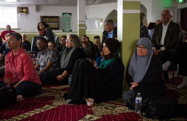 Melissa Alkassir, from right, and Amatullah Malki, 16, listens with a large audience to a presentation explaining Muslim customs, beliefs, and misconceptions during an open house Saturday, Feb. 18, 2017 at the Denver Islamic Society.