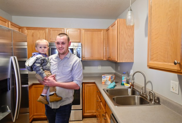Thomas Moran holds son Jackson Moran, 16 months old, inspects the kitchen on a walk-through of a town home