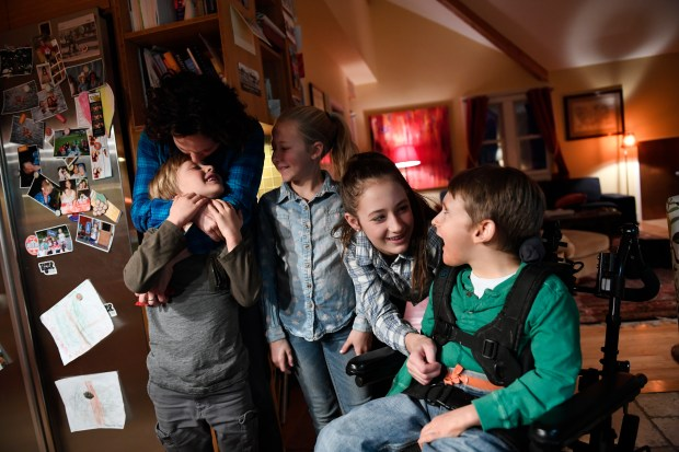 Megan Reamer kisses her son Charlie, 7, while Olivia, 10, middle Ella, 14 and Jackson, 15, right, hang out together at their home on Jan. 10, 2017 in Crested Butte.