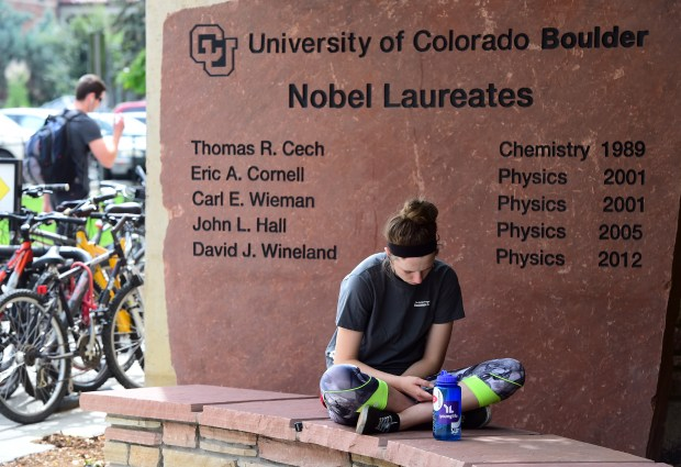 Emily Davis reads in front of the sandstone Nobel Laureates list near Duane Towers on the University of Colorado Boulder campus.