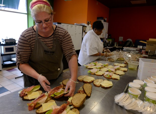 Donna Dickens, left, and Kathrine Lewis, prepare sandwiches together inside the Share Good Foods kitchen in Englewood on Feb. 1.