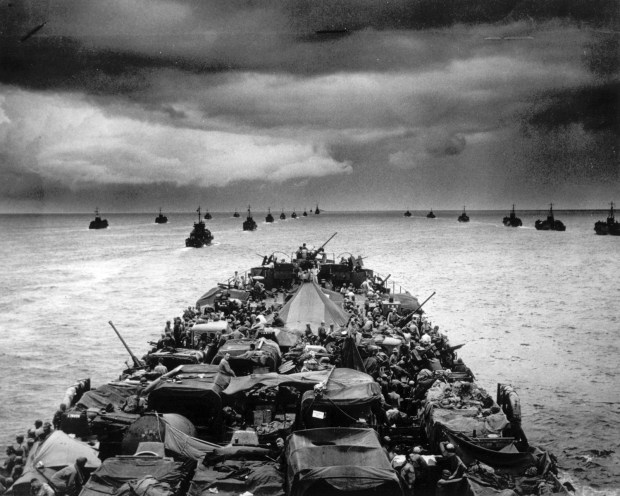 July 1944: Columns of troop-packed LCIs trail in the wake of a Coast Guard-manned transport ship en route for the invasion of Cape Sansapor, New Guinea. The deck of the LST is densely packed with heavy military machinery and other war supplies.