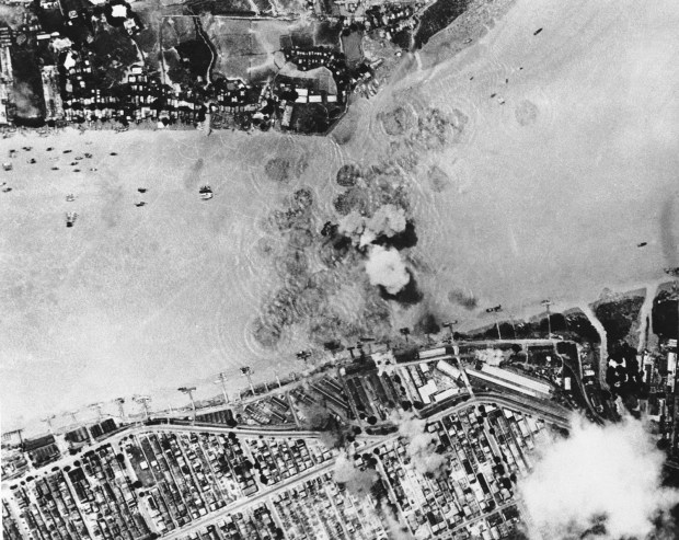 Nov. 11, 1943: A supply ship, one of two that the Japanese were able to work through U.S. Air attacks, explodes in Rangoon Harbor (center) after a direct hit by a bomb from a Tenth U.S. Air Force Plane. Hits also were scored on port facilities, seen smoking (top center). Note numerous small craft moored at docks and offshore, (right).