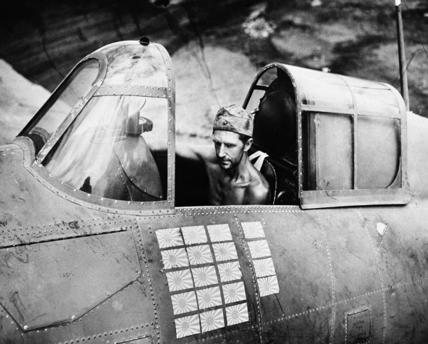 March 22, 1943: Technical Sgt. R.W. Greenwood, a Marine, sits in the cockpit of a Grumman Wildcat fighter plane, based at Henderson Field, Guadalcanal, that is credited with shooting down 19 Japanese aircraft, as illustrated by the number of Japanese flags on his plane. Several different pilots have flown the ship during successful missions, but Sgt. Greenwood has remained plane captain.