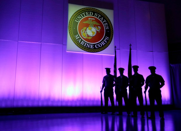 In this May 5, 2014, file photo, a U.S. Marine Corps Color Guard stands under a Marine Corps emblem in Jupiter, Fla. The Defense Department is investigating reports that some Marines shared naked photographs of female Marines, veterans and other women on a secret Facebook page, some of which were taken without their knowledge.