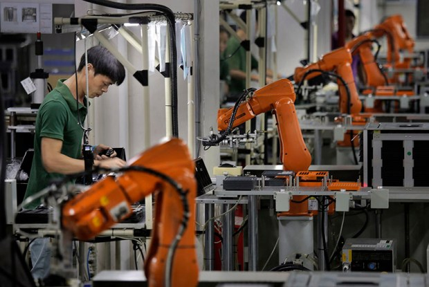 A man works amid orange robot arms at a factory in the southern Chinese industrial boomtown of Shenzhen.
