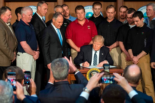 "Surrounded by miners from Rosebud Mining, President Donald Trump signs the Energy Independence Executive Order at Environmental Protection Agency headquarters in Washington on Tuesday. Trump claimed an end to the ""war on coal"" as he moved to roll back climate protections enacted by President Barack Obama."