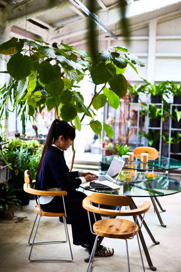 "Artist Takahashi Kiroko on the 2nd floor of her studio working while surrounded by plants in Tokyo. The photo is featured in the book ""Where They Create,"" which explores people and their creative studios."