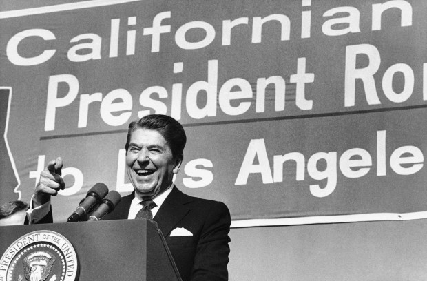 President Ronald Reagan points toward ...