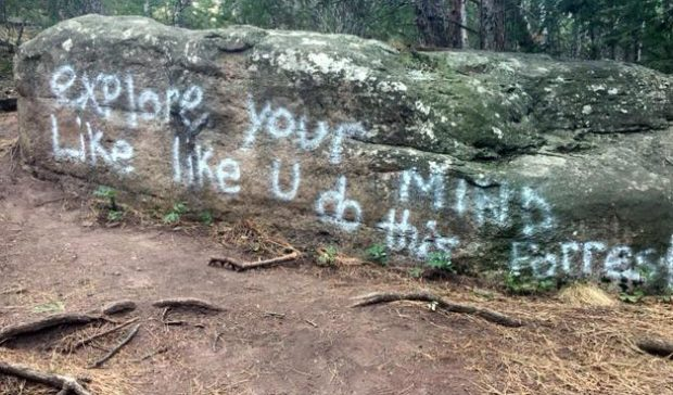 A summons has been issued to two visitors from out of state for allegedly leaving this graffiti on a rock alongside Boulder's Saddle Rock Trail.