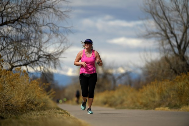 A runner moves along the Cherry Creek Trail