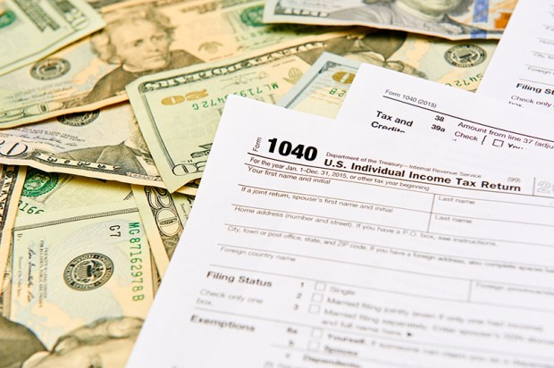 1040 Individual Tax Return form on top of a table full of paper money.
