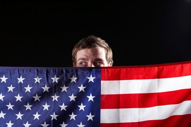 Suspicious man peering over American flag
