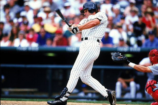 Dante Bichette #10 of the Colorado Rockies swings at the ball during the game against the St. Louis Cardinals at Coors Field in Denver, Colorado.